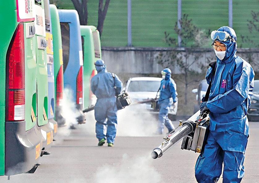衞生人員昨天在首爾一個巴士站噴灑消毒劑防疫。法新社