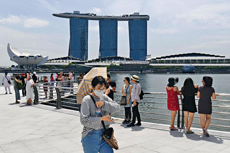 新加坡疫情嚴峻,遊客戴口罩遊覽濱海灣 一帶。 法新社