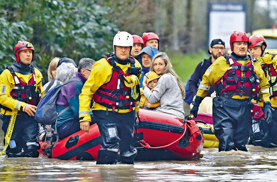 在威爾斯楠特加魯村,救援人員協助居民撤離。 美聯社