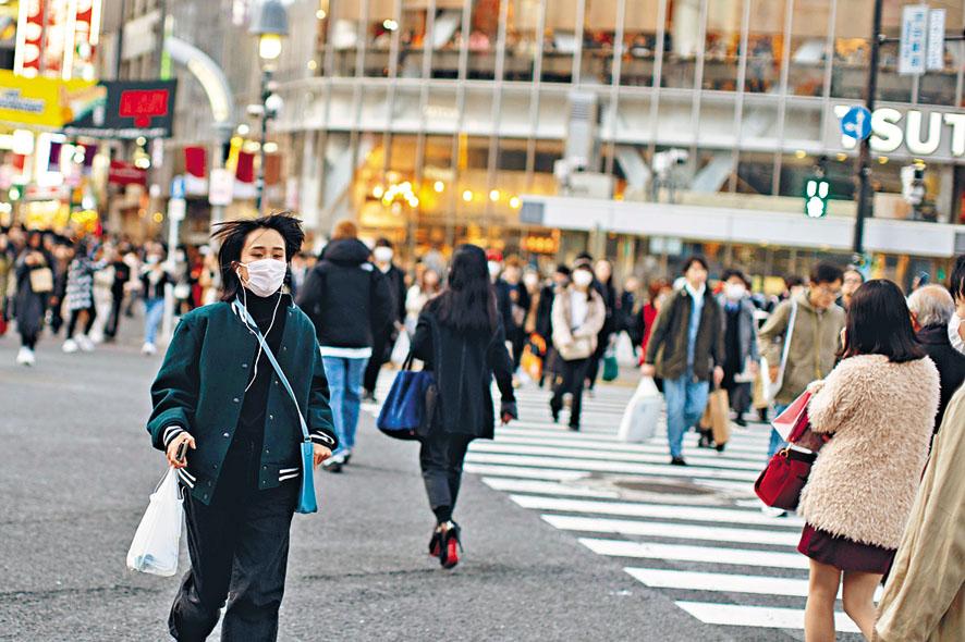 日本涉谷街頭昨日有女性戴 口罩。 路透社