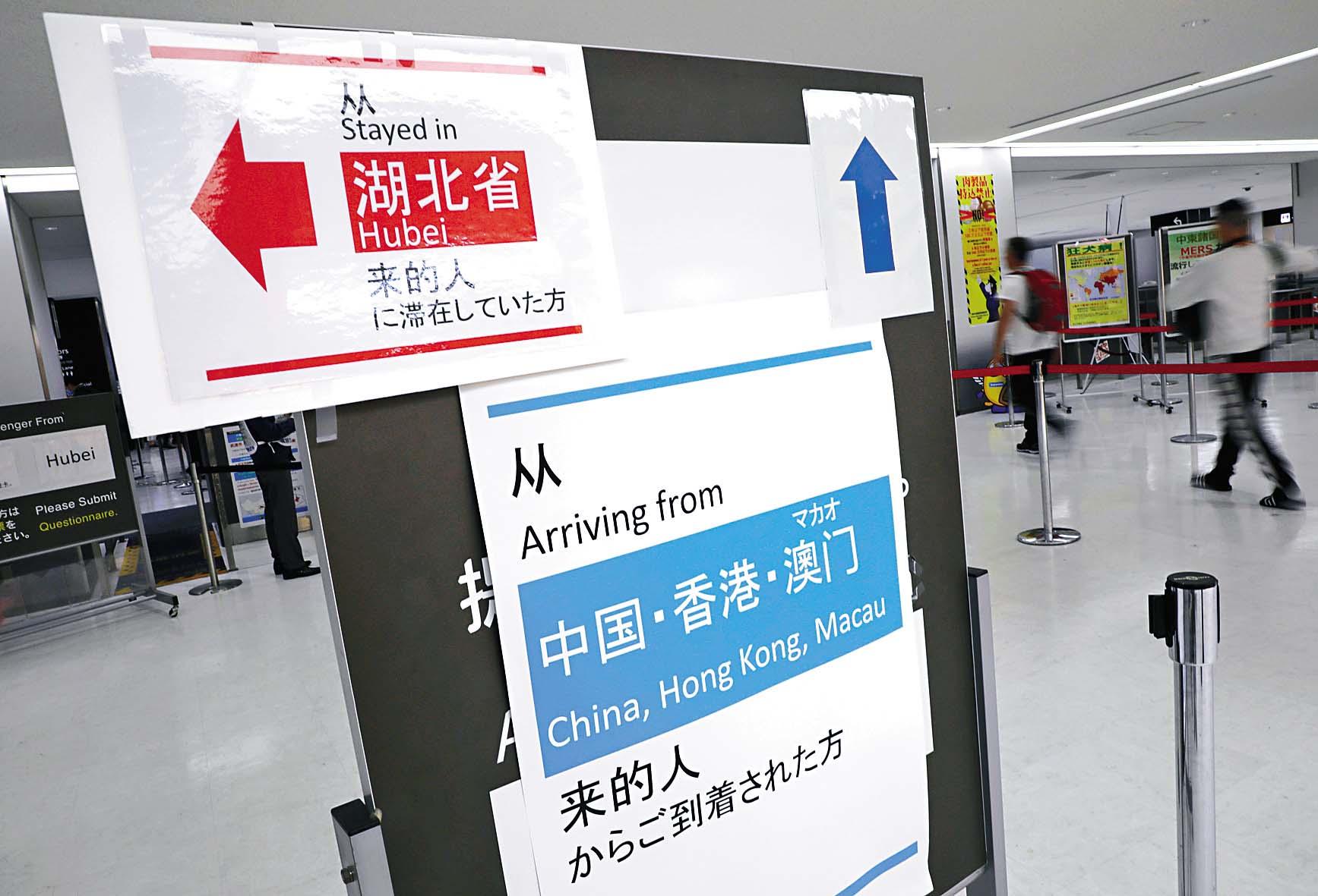 東京成田機場有標語牌指示來自湖北及中港澳旅客,前往申報健康狀況的地點。 路透社
