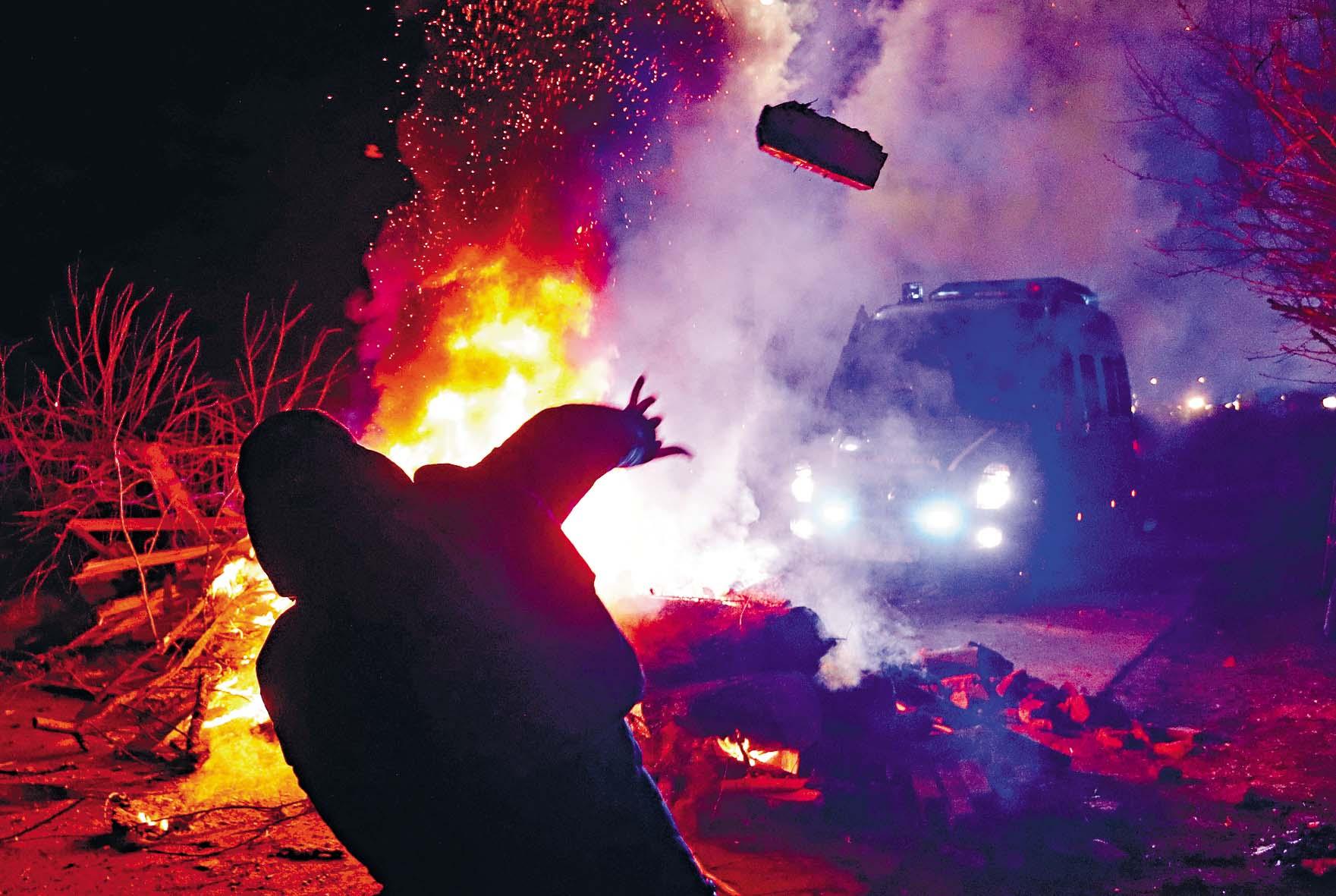 新桑扎里鎮一名示威者周四 向警車擲石,抗議該鎮醫院被 闢作隔離設施。  路透社