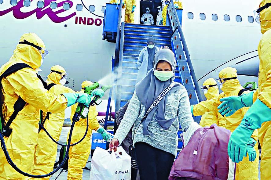 ■醫護人員周日在新加坡附近的印尼巴淡島韓那丁國際機 場,為武漢撤返的印尼人噴消毒劑。  美聯社