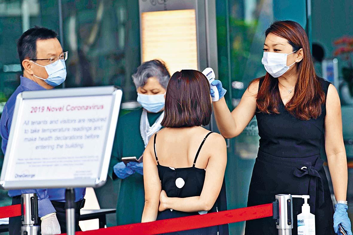 新加坡金融區一幢大廈的管理公司職員,為租戶和訪客檢測體溫。 法新社