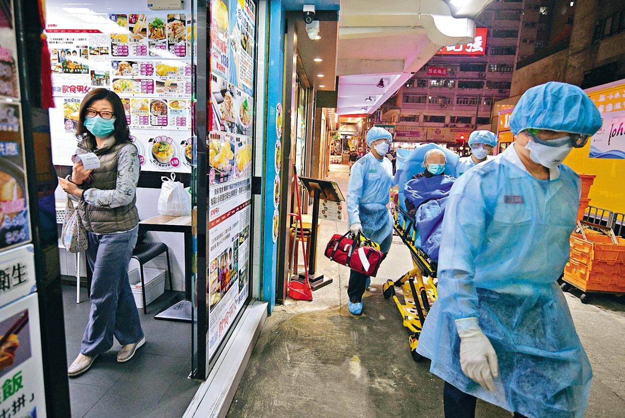 衞生署人員昨夜到美輪大廈接走一名婆婆時,街坊走入店鋪內暫避。
