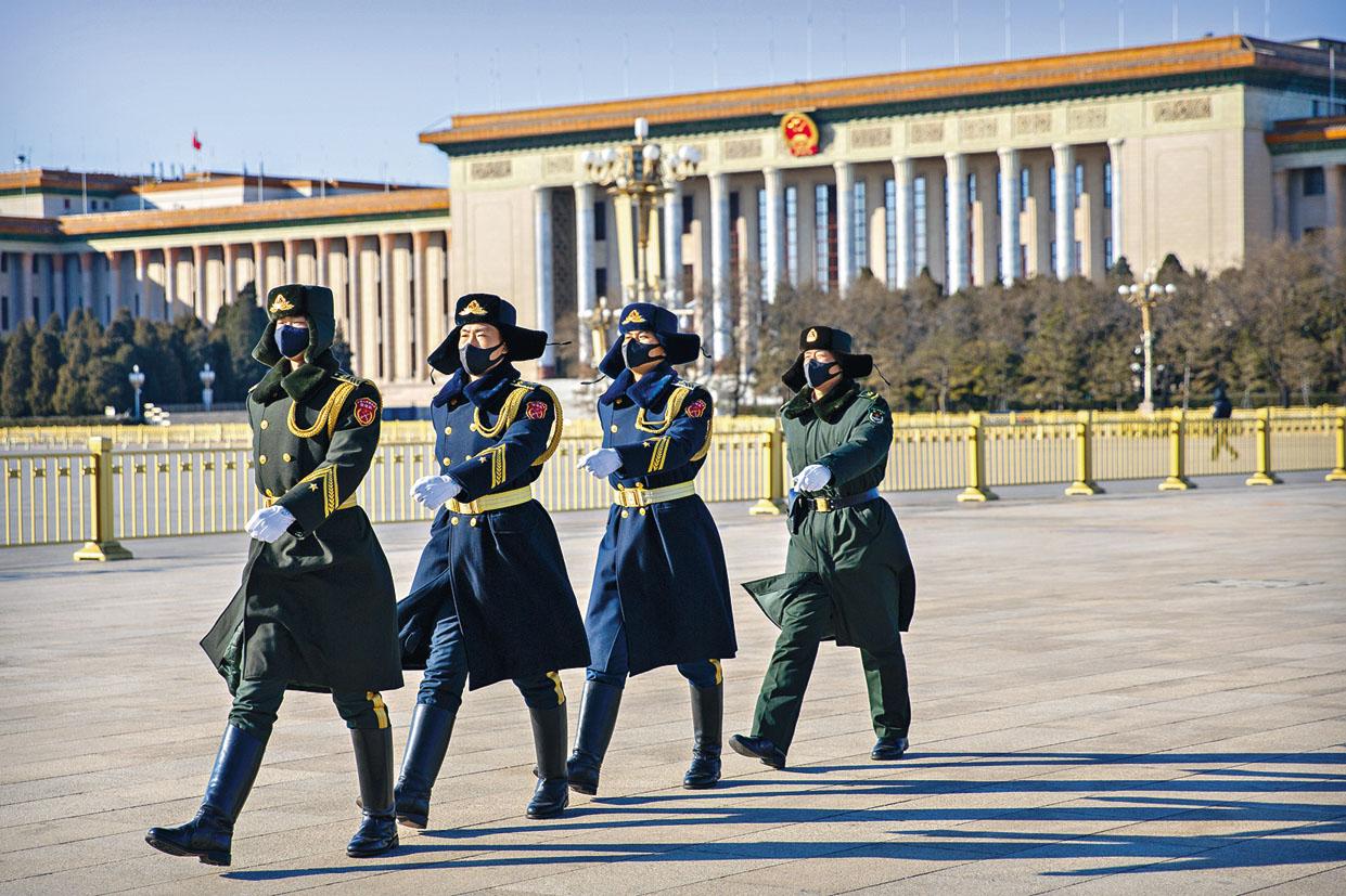 原定於三月初開幕的全國兩會將 押後。圖為戴着口罩的武警人員在 北京人民大會堂前走過。 美聯社