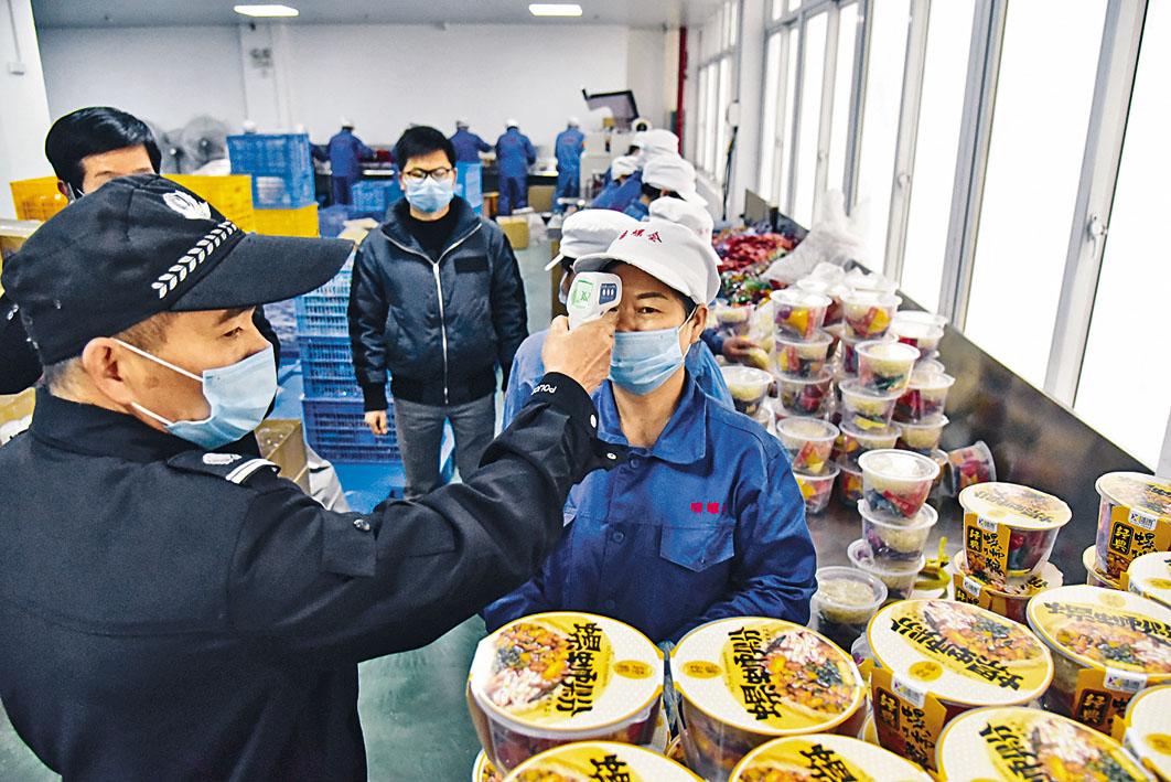 廣西一企業復工,對工人測量體溫。