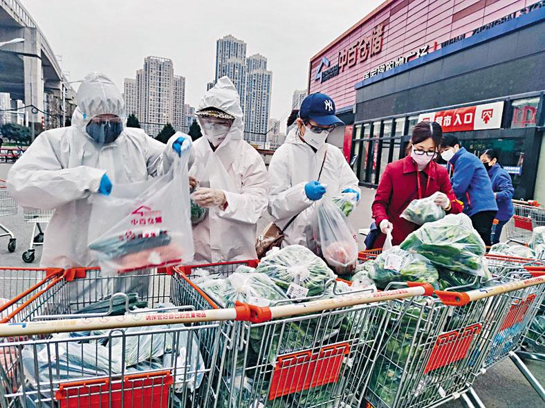 武漢仍有社區工作人員到超市採購, 送貨到被隔離人員家中。  路透社
