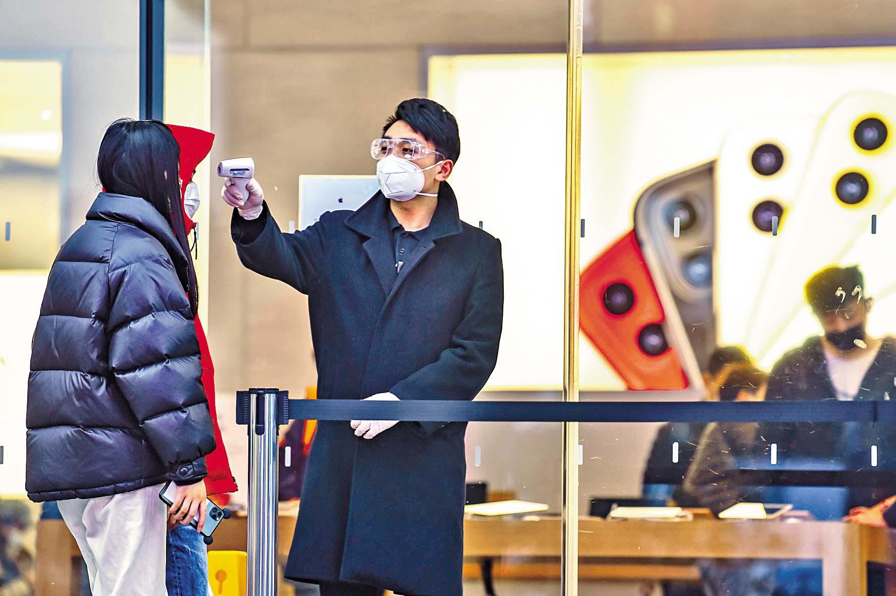 ■蘋果上海門店的保安人 員為顧客探熱。 法新社
