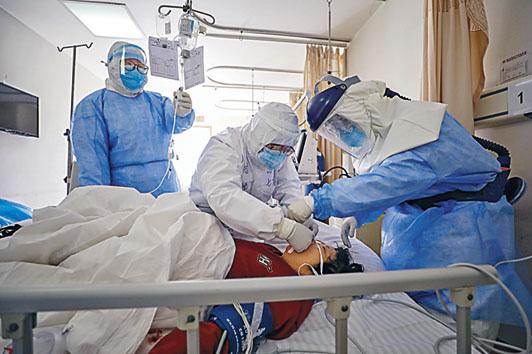 武漢醫護人員在醫治新冠肺炎病人。 美聯社