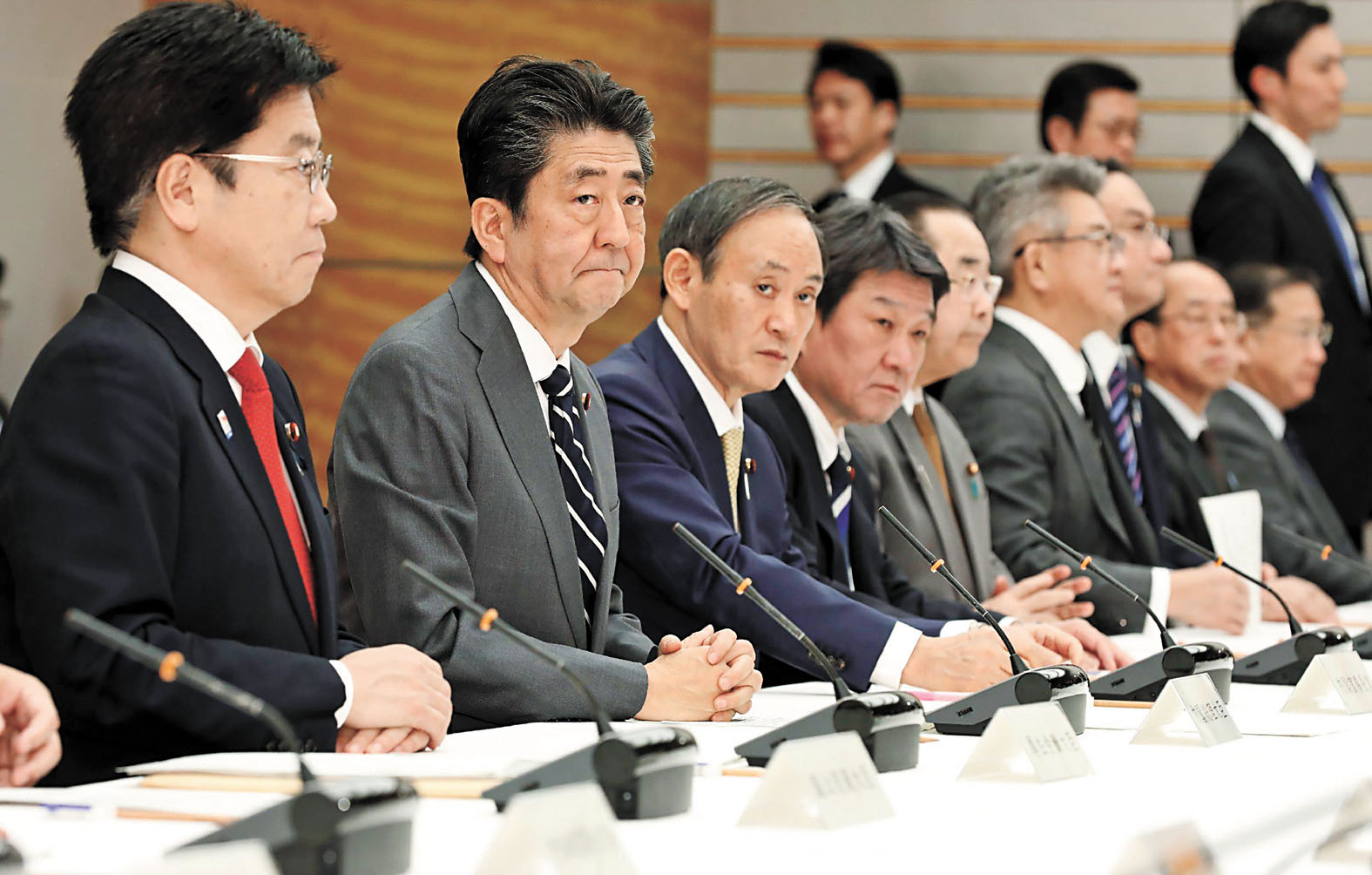 日本首相安倍晉三(左二)和厚生勞動大臣加藤勝信(左一)出席有關新冠肺炎的會議。美聯社