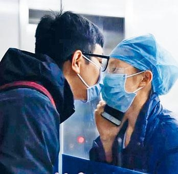 護士陳穎隔着玻璃和男朋友相吻。
