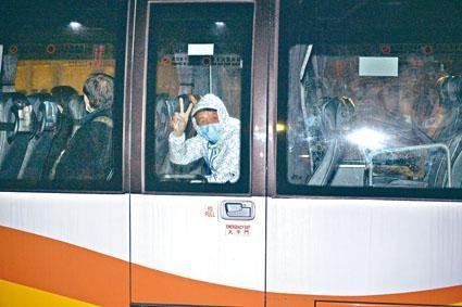 一名前往駿洋邨接受隔離的男子,向傳媒展示勝利手勢。