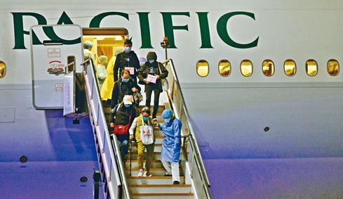 第二批坐包機由日返港的82名港人昨晨抵埗落機,準備坐上前往隔離營的專車。