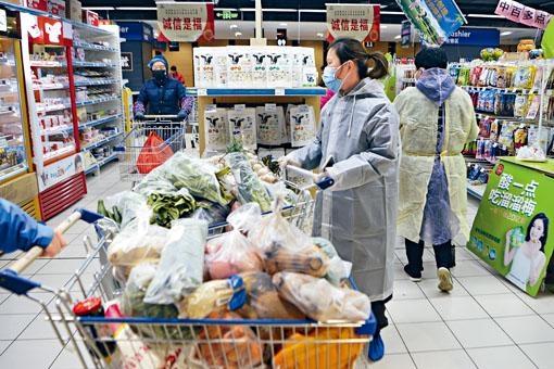 武漢市民身穿防護衣到超市採購日用品。