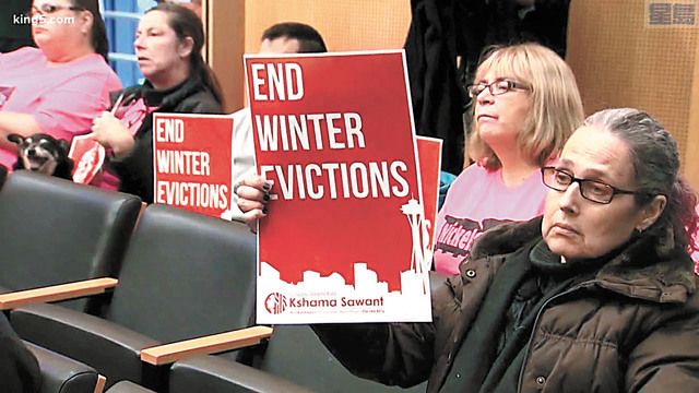 西雅圖市議會通過法案禁冬季驅逐租客。圖為支持法案的民眾早前在市議會舉牌表達立場。資料圖片