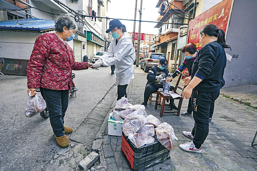 武漢菜市場工作人員為居民探熱,不敢鬆懈。 美聯社