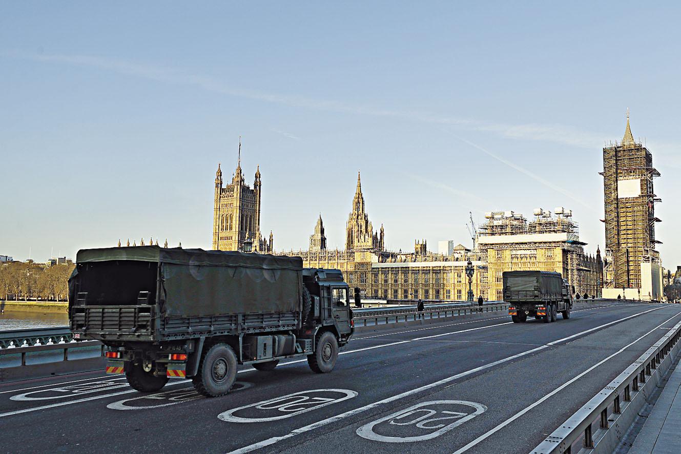 倫敦西敏橋上周二可見運送醫療物資的軍車,駛向國會大樓。