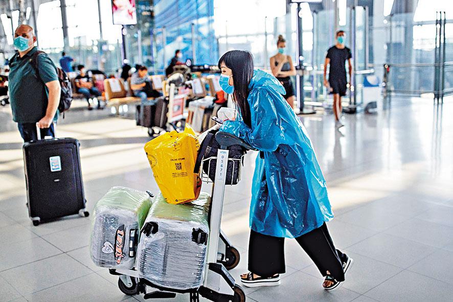 曼谷國際機場昨日有旅客戴口罩兼穿塑膠保護衣防疫。
