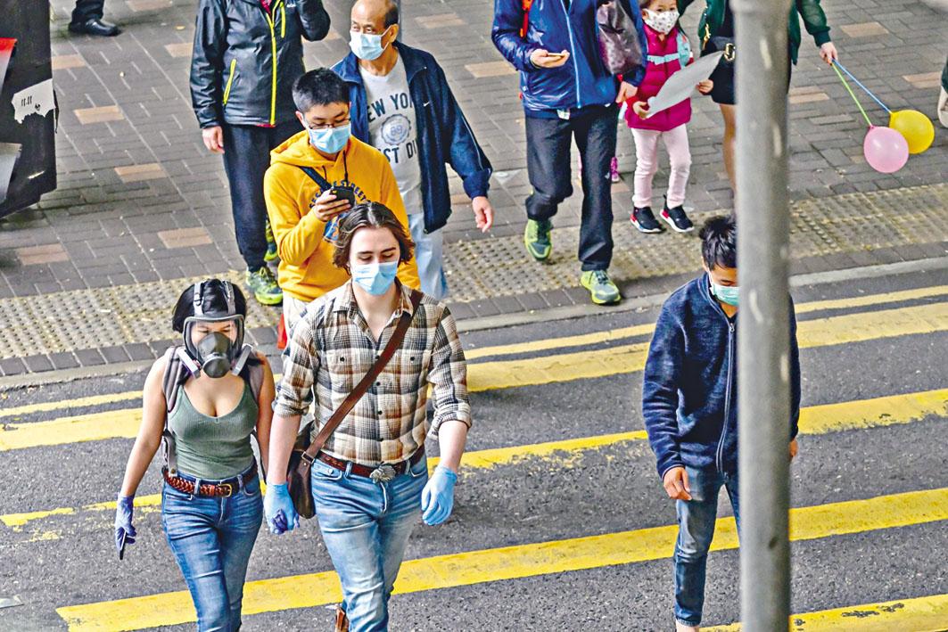 近日天氣回暖,街上行人即使換季,也不忘佩戴防疫裝備。