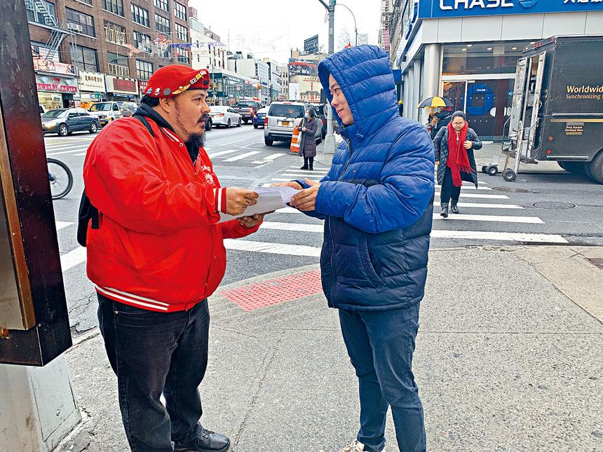 梅賈斯在華埠街頭派發傳單,告知人們「守護天使」將在華埠巡邏,預防並阻止仇恨犯罪。