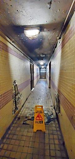 起火電動輪椅在走廊猛烈燃燒,牆壁嚴重熏黑。