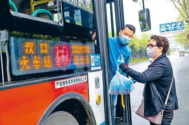 武漢市部分公交車恢復開行,市民須掃二維碼上車。
