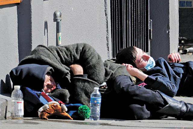 西雅圖市中心Union Gospel Mission庇護所外,有帶著口罩的無家者睡臥街頭。美聯社
