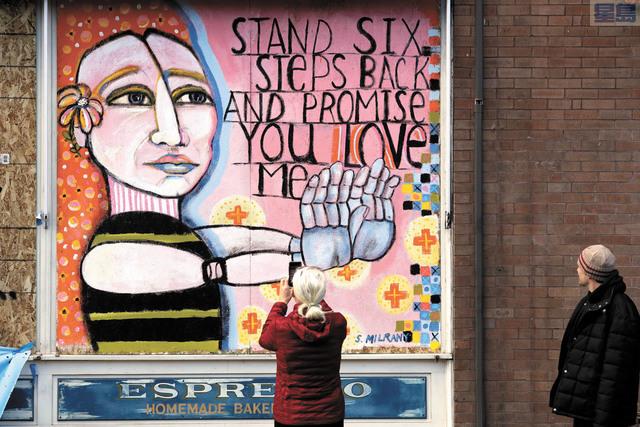 西雅圖一家歇業餐館外牆釘上木板,藝術家繪製巨幅壁畫,呼籲民眾相互之間保持6尺社交距離。美聯社