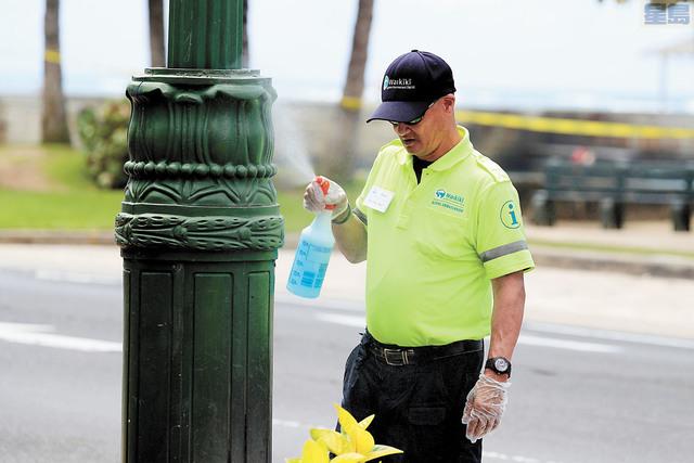 夏威夷實施居家避疫令。圖為工作人員在沙灘清潔消毒公共設施。美聯社資料圖片