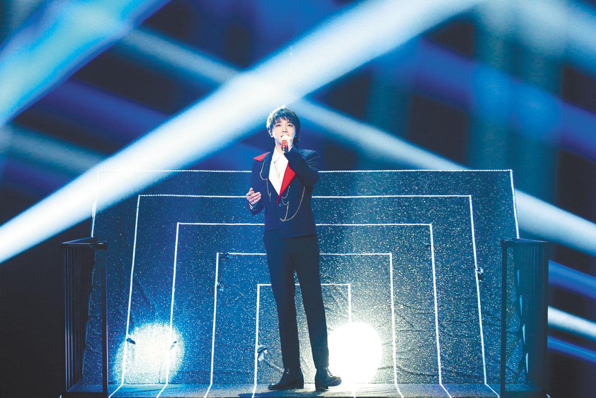 華晨宇拿著紅色話筒在舞台上表演改編後的《咱們屯裏的人》歌曲。 網上圖片