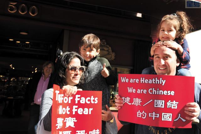 遊客們紛紛拿上遊行隊伍的標語,表示支持。記者黃偉江攝
