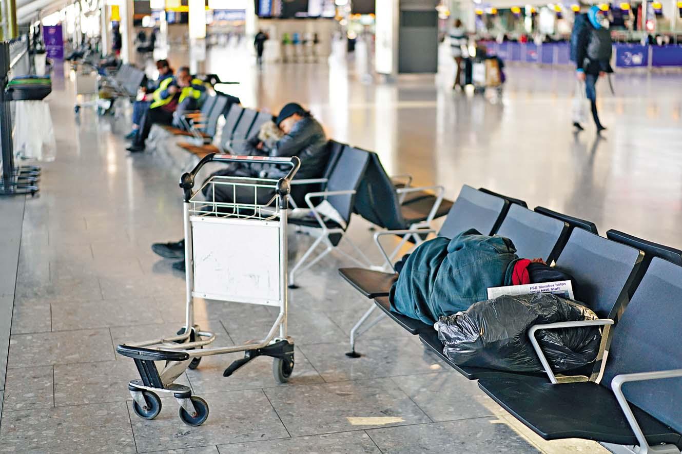 在新冠疫情肆虐下,一些受防 疫管制措施影響的旅客,在倫敦 希斯路機場睡覺。  路透社