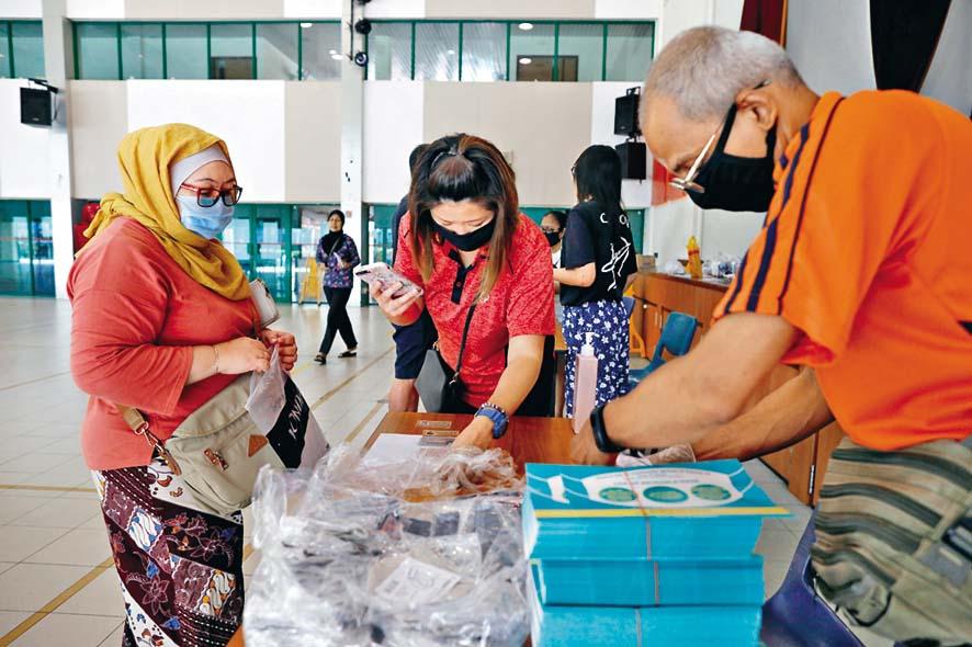 新加坡民眾昨日在社區中心內,索取政 府免費派發的可重用口罩。 路透社