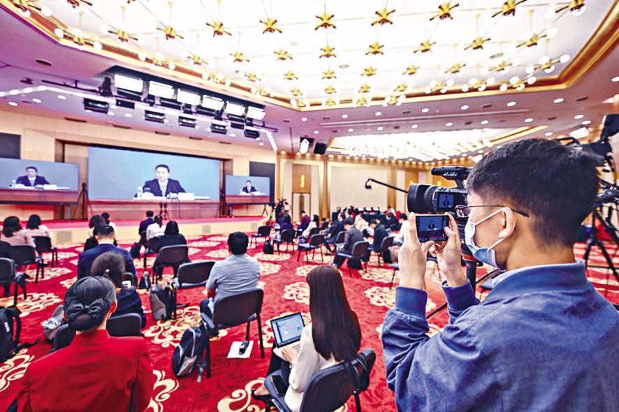 全國政協新聞發言人郭衛民介紹大會 有關情況,記者人數設限,座位之間亦 保持距離。 中新社
