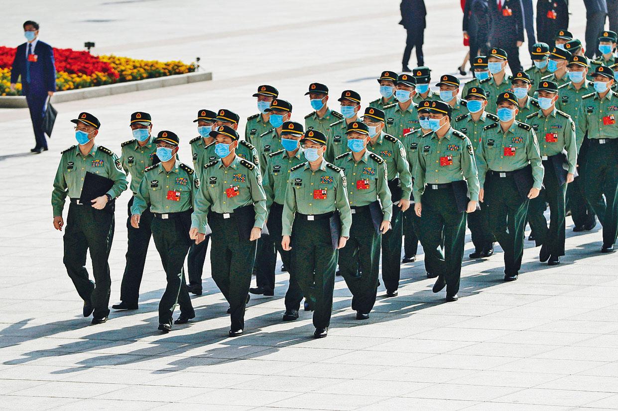 軍隊代表們戴着口罩參加人大開幕。 路透社