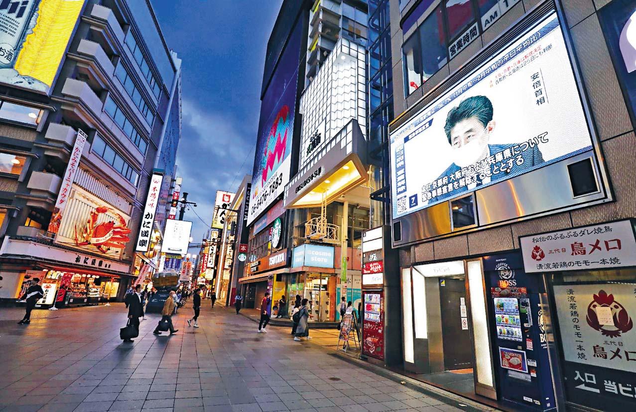 大阪街頭的電視屏幕,周四播放安倍晉 三宣布數大城市解除緊急事態。 法新社