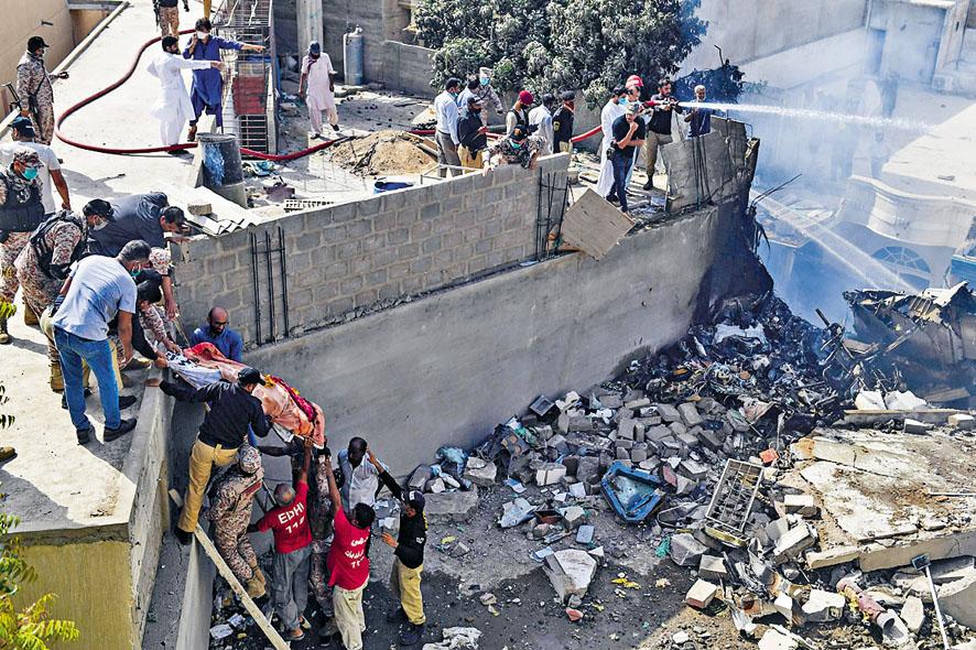 救援人員從瓦礫堆中抬走遇難者遺體。 法新社