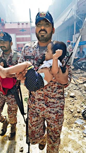 救援人員在墜機現場抱走一 個男孩。 互聯網