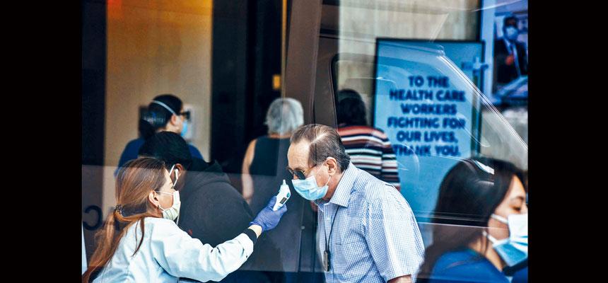 圖為一名男子在被允許進入紐約市西奈山醫院大樓之前,需要檢查體溫。紐約州的疫情尚未穩定,並未出現官方預期的跌勢。法新社