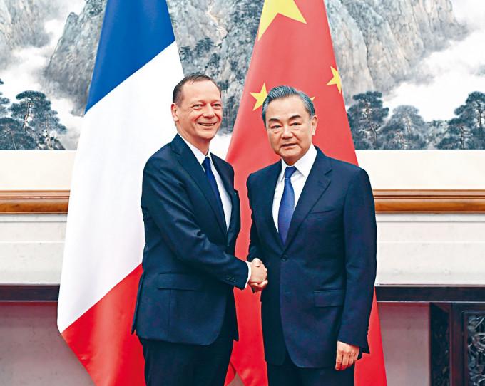 王毅(右)前日與法國總統外事顧問博納通電話。