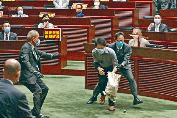許智峯到主席台前投下發出惡臭的腐爛植物,所有議員隨即疏散。