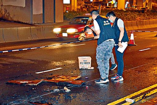 警方在觀塘道檢視遺在路中的石油氣罐。
