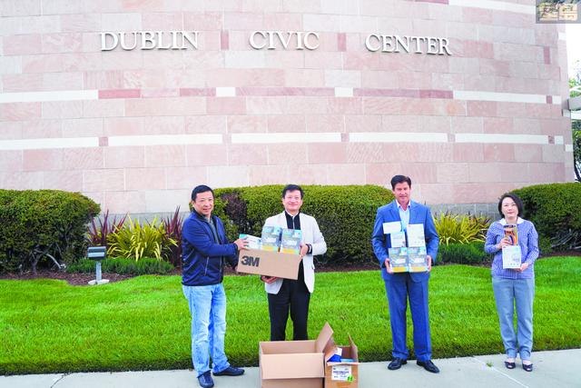 美國潮商基金會理事長林志斯(右2)向都布林市市長郝伯特(右2)送交1200個口罩。美國潮商基金會提供圖片