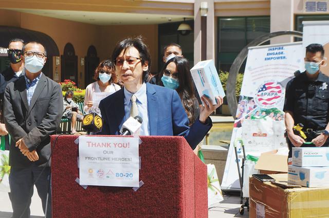 屋崙華埠商會會長陳錫澎手持一次性醫用口罩,表示將捐出。記者劉玉姝攝
