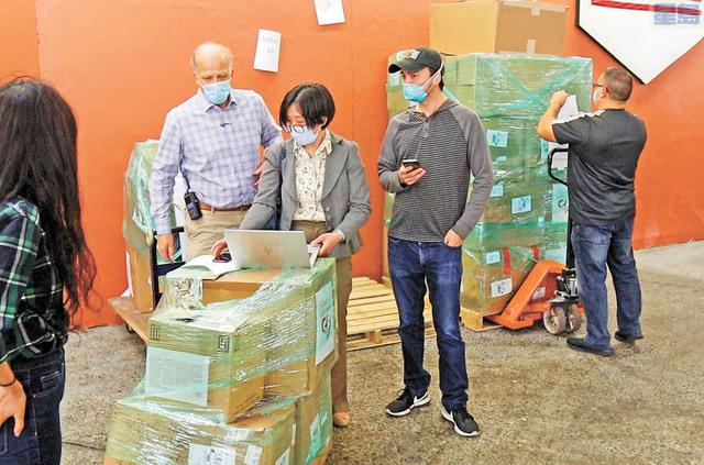 灣區各教會義工領取口罩準備捐贈各地。記者王慶偉攝