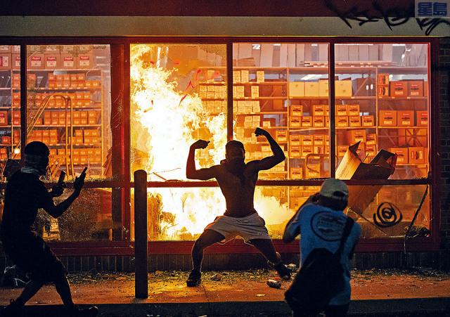 明州一非裔男子遭警員壓頸致死事件掀起民憤,州內連續兩晚發生暴亂,圖為示威者搶劫破壞店鋪並縱火。美聯社