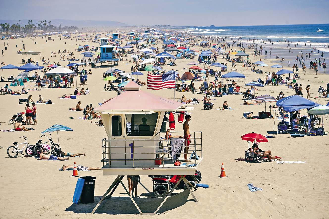 美國多個州份陸續解除「居家令」,大批泳客 上周六到加州亨廷頓海灘暢泳。  美聯社