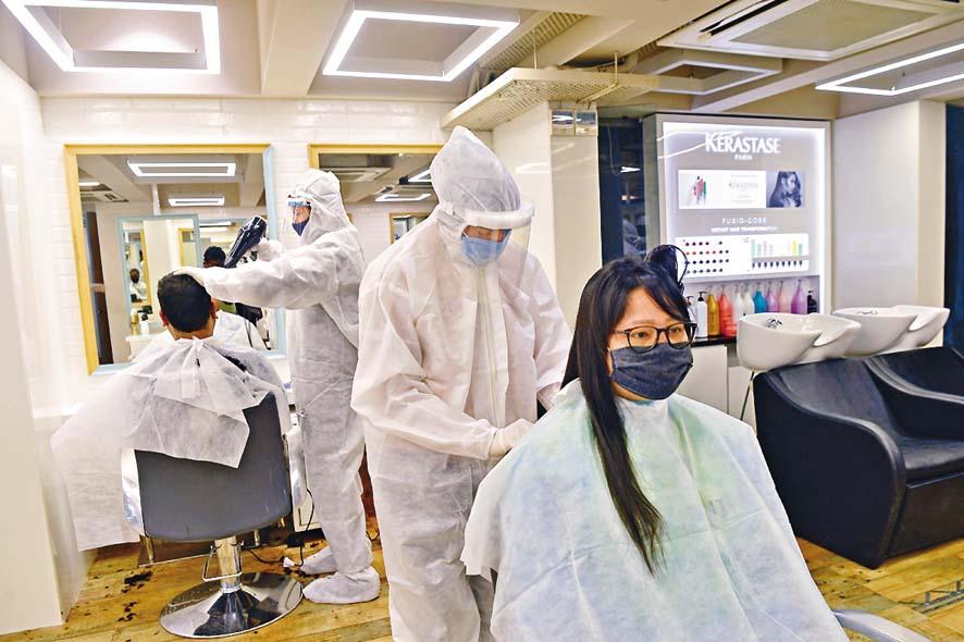印度孟買一間理髮店昨天重開,理髮師穿上保護衣和面 罩替客人服務。  法新社