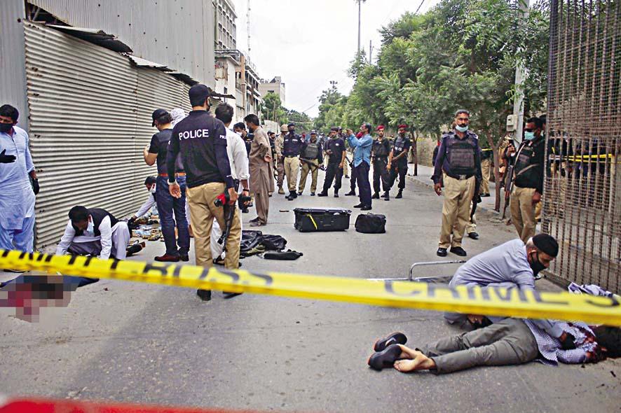 安全人員周一在巴基斯坦證交所外檢查槍手 的屍體。 美聯社